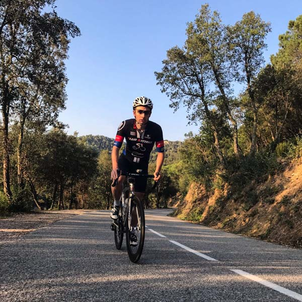 Cyclist climbing uphill at dusk on Els Angels climb Girona