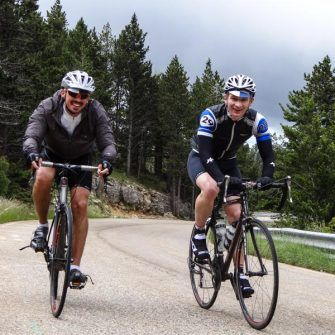 Two cyclists climbing Mont Ventoux, nearing the end of the forest
