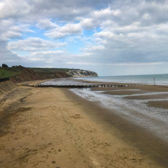 Sandown beach which is wide and sandy with the coast heading into the distance