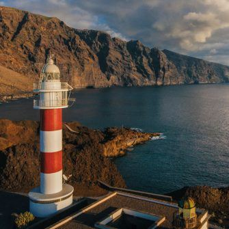 Punto de Teno lighthouse against orange cliffs at dusk