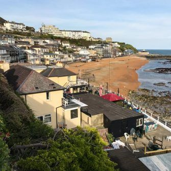 Golden sands of Ventnor beach with the town backdrop stretching up the cliff behind