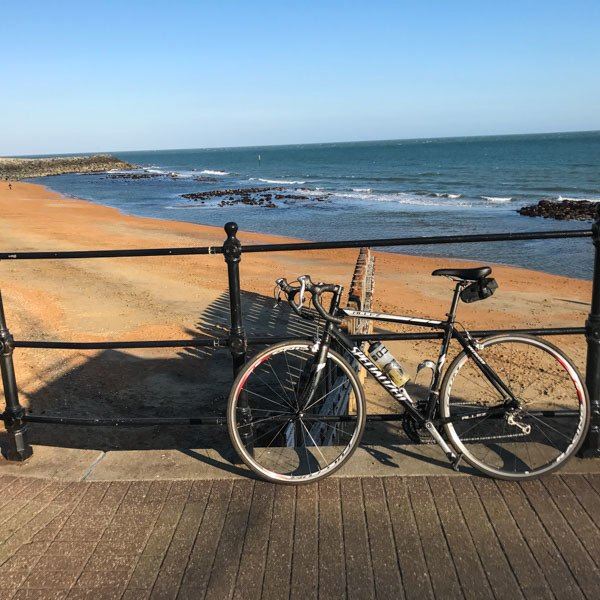 Golden sands with bicycle in front of railings at Ventnor esplanada