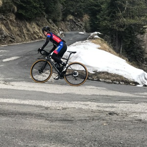 Snow on the road near the top of the Col de Turini with cyclist in foreground