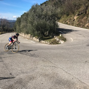 Cyclist taking on a wide hairpin in the Alpine foothills near Nice