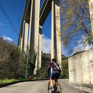 Cycling under the concrete arches of the motorway bridge near the bottom of the Col de la Madone climb