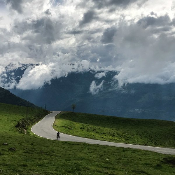 Cyclist on open road near top of Hautacam with thick cloud above