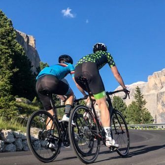 Two men wearing Stolen Goat bib shorts with blue and green bands at leg