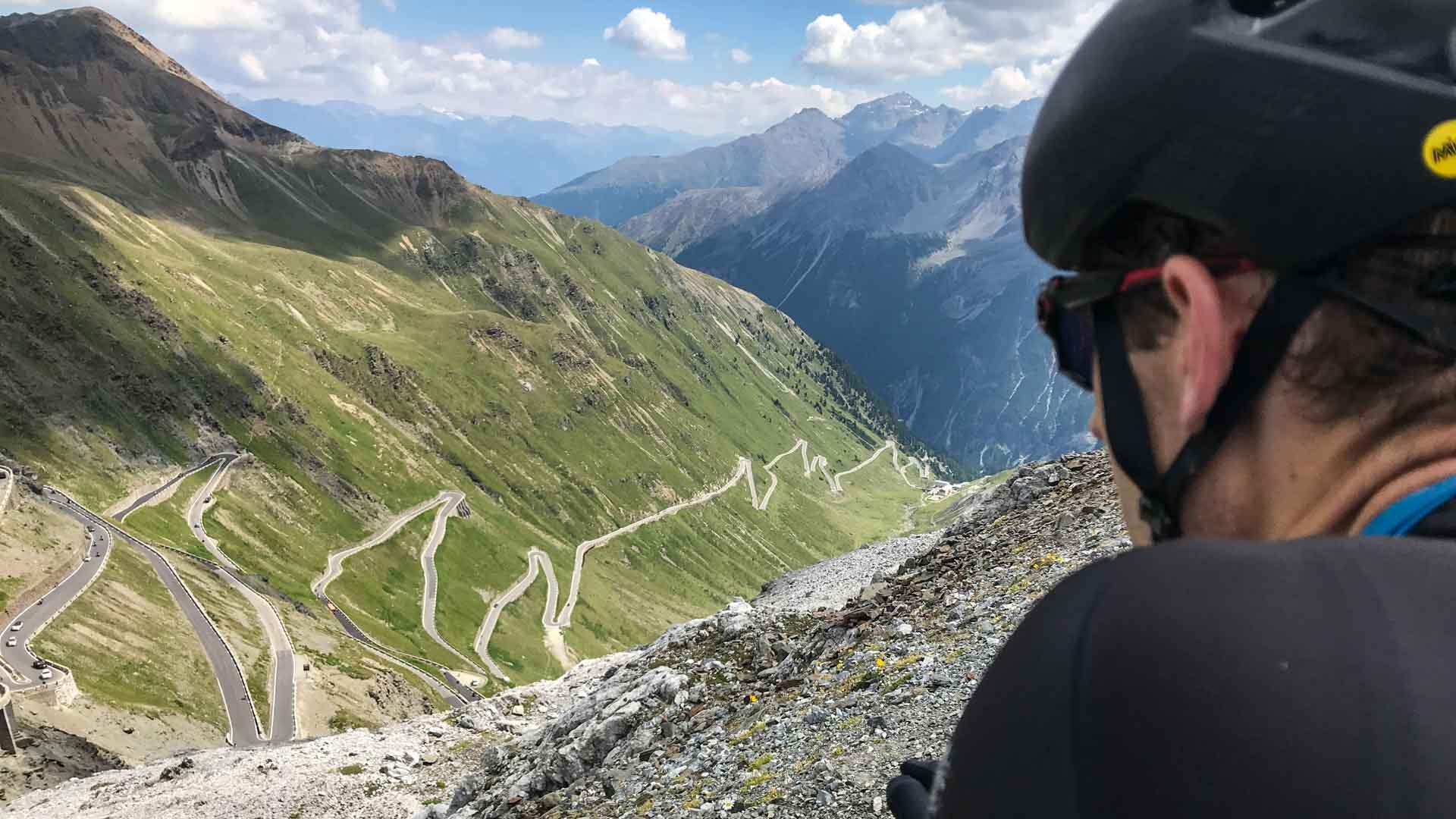 Passo dello Stelvio cycling cyclist admires view from top of Passo dello Stelvio