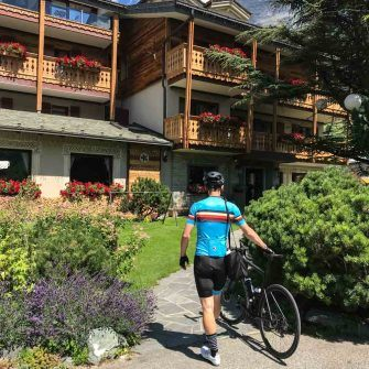 Cyclist walking into cycling friendly hotel Bormio