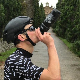 Black and white water bottle in use by cyclist