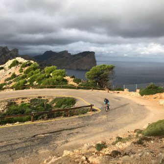 cyclist on the cap de formentor cycling route, Mallorca, approaching the lighthouse