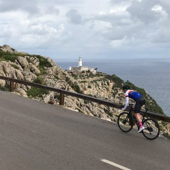 Cyclist cycling the cap de formentor cycling route on Mallorca with lighthouse in distance
