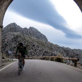 Cyclist coming through arch on Mallorca's iconic Sa Calobra climb
