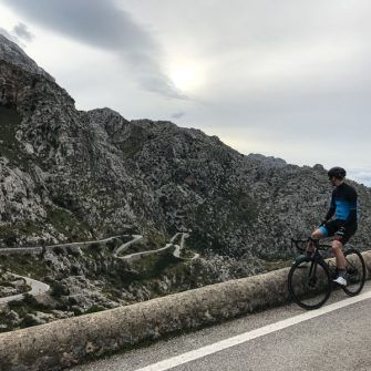 Cyclist admiring view of switchbacks on Sa Calobra, Mallorca