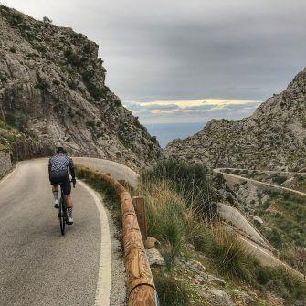 Cyclist cycling down Sa Calobra's twists and turns