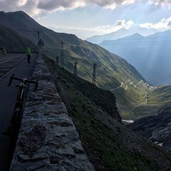 View down the Stelvio with bicycle in foreground, very early in the morning