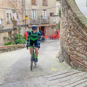 Cyclist climbing twisting, steep streets of villages of the Costa Daurada
