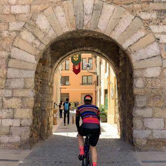 Cyclist cycling through medieval arch into Montblanc, costa daurada
