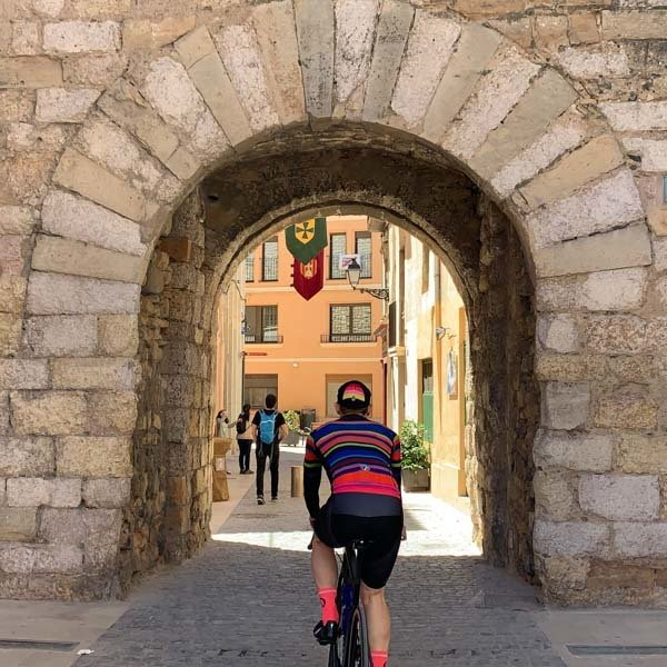 Cyclist cycling through medieval arch into Montblanc, costa daurada