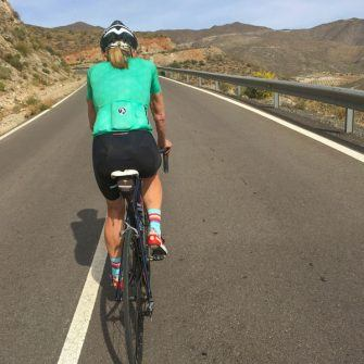 Cyclist in green jersey cycling on quiet road, Almeria