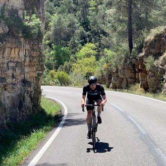Cyclist beside craggy cliff wall, costa daurada