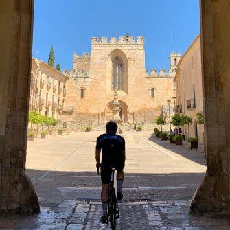 Cyclist entering Santa Creus monastery building complex