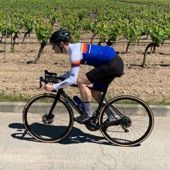 Cyclist in front of vines