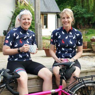Two women wearing stolen goat cycling jerseys