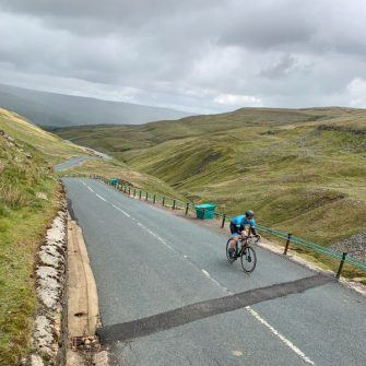 Cyclist at the summit of Buttertubs Pass, Yorkshire Dales