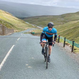 Cyclist climbing the Buttertubs Pass by bike, Yorkshire Dales