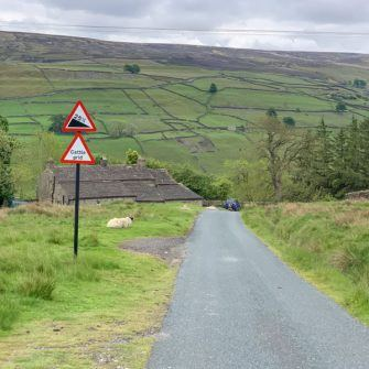 Descent towards Long Row with warning sign for very steep road