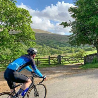 Cyclist cycling through Coverdale, Yorkshire Dales