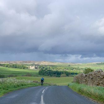 Cyclist with views to Castle Bolton, Yorkshire Dales