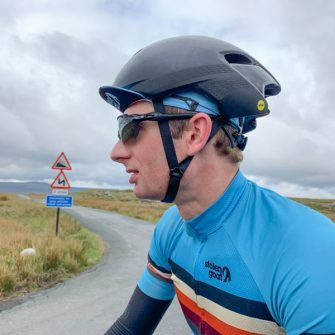 Cyclist at summit of Tan Hill, Yorkshire Dales