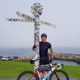 Cyclist and John O Groats sign, on the North Coast 500 route