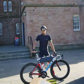 Cyclist at Inverness castle after completing the NC500 cycle route