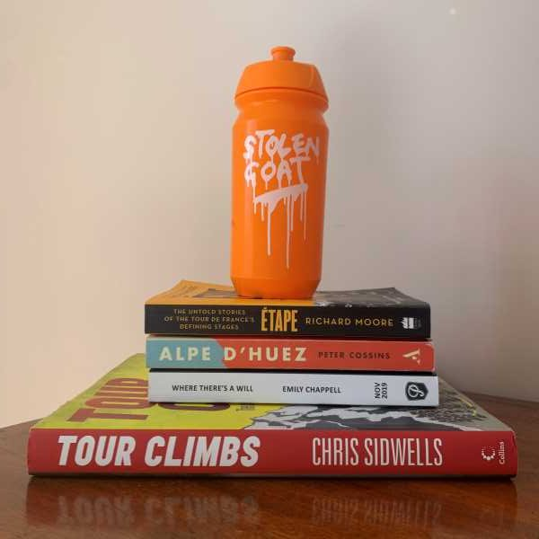 Pile of the best cycling books with stolen goat bottle on top
