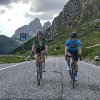 Two cyclists at summit of Dolomites cycling climb Passo Pordoi