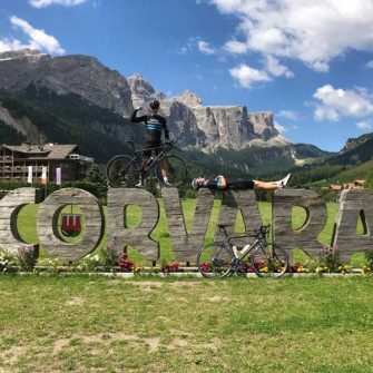 Two cyclists on Corvara sign