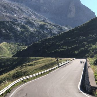 Cyclists cyclin gup Passo Fedaia. Dolomites Italy