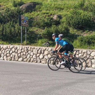Two cyclists at summit of Passo Fedaia Italian Dolomites
