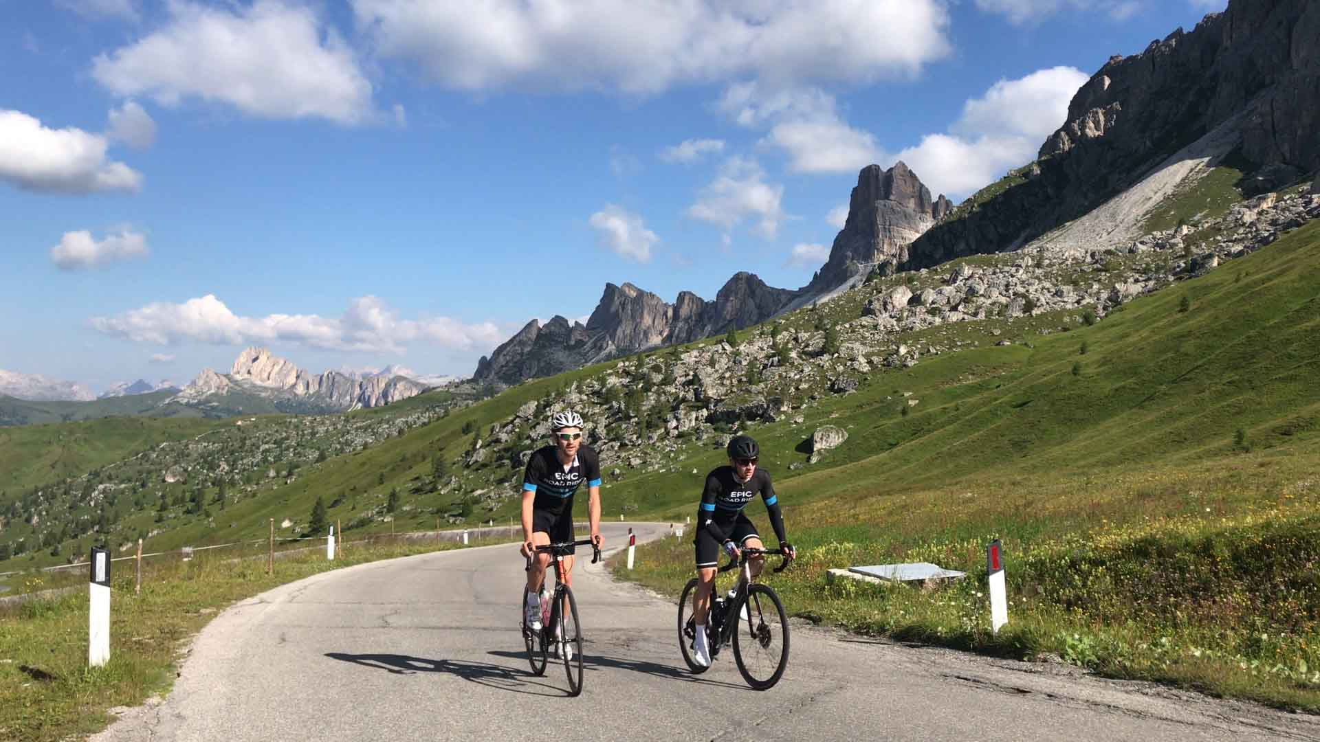 Two cyclists cycling up Passo Giau, Dolomites, Italy