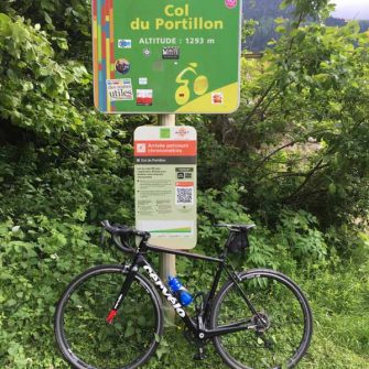 Cyclist's bike on the Col du Portillon summit sign