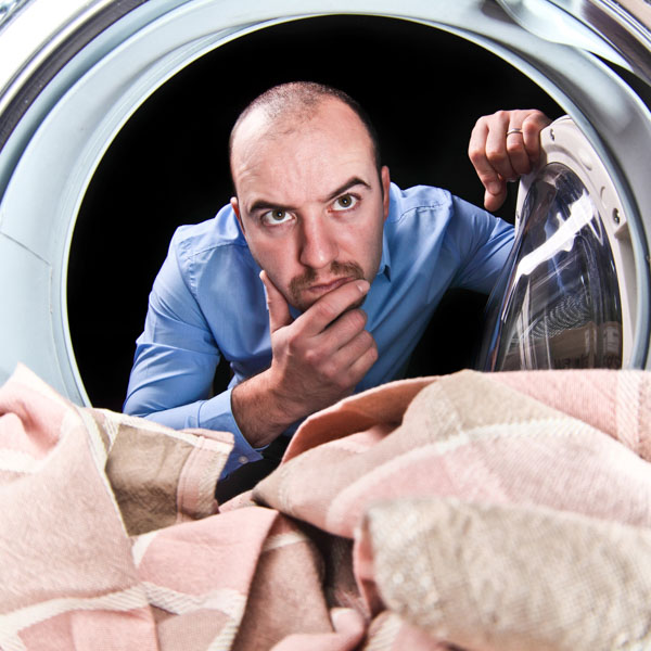 Man looking into a tumble dryer