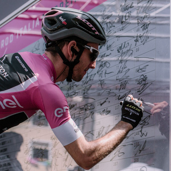 Pro cyclist in Giro d'Italia pink jersey signing on