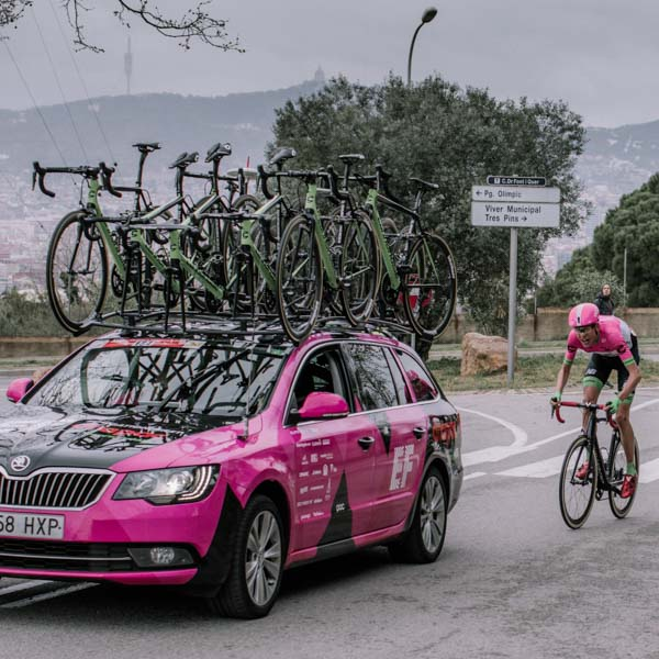 Pro cycling team car with bikes and rider behind