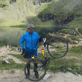 Cyclist in front of Balea Lake on the Transfagarasan highway