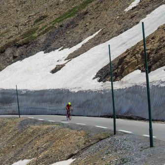 Cyclist on road surrounded by snow in the French Alps