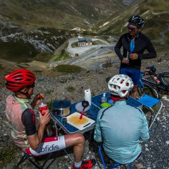 Cyclists eating lunch on the route des grandes alpes cycling tour