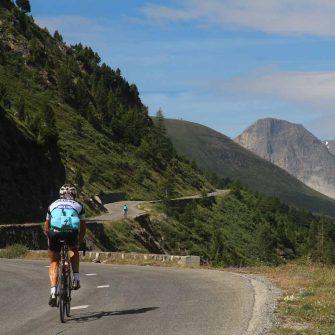 Cyclist cycling up an Alpine Pass